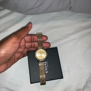Coach gold watch with diamonds around it,
